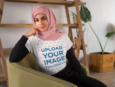 T-Shirt Mockup of a Woman with a Hijab Sitting on a Couch 28271