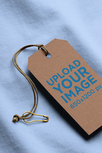 Minimal Mockup Featuring a Cardboard Brand Tag Lying on a Solid Color Fabric 27636
