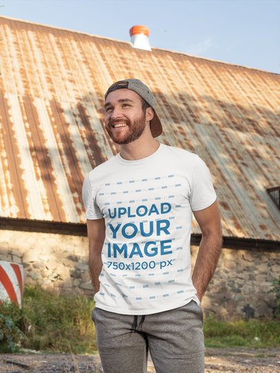 T-Shirt Mockup of a Man Posing in Front of an Old Structure 28199