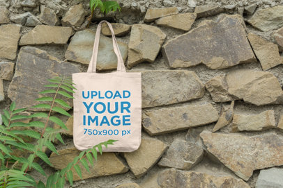 Mockup of a Bag Hanging on a Stone Wall by Some Plants 110-el