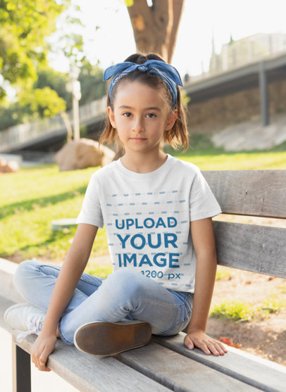 T-Shirt Mockup of a Girl Sitting on a Bench at the Park 28072