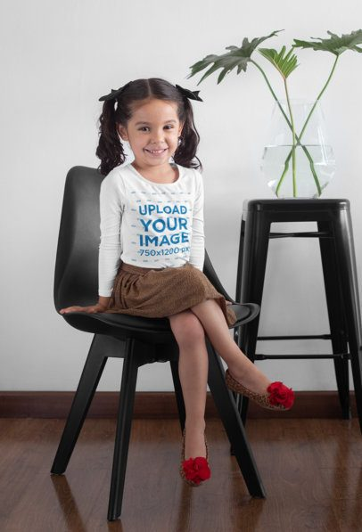 Long Sleeve Tee Mockup Featuring a Girl Sitting on a Chair Next to a Plant 28099