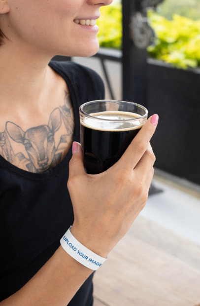 Paper Wristband Mockup Featuring a Woman Holding a Pint of Stout 28219