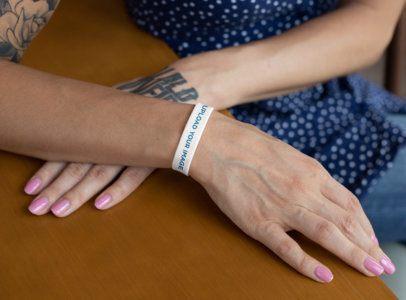 Mockup of a Tattooed Woman Wearing a Silicone Wristband 28224