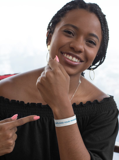 Mockup of a Joyful Woman Pointing at Her Paper Wristband 28243