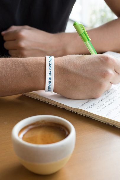 Silicone Wristband Mockup Featuring a Man Writing at a Cafe 28248
