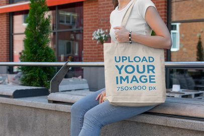 Tote Bag Mockup of a Woman Sitting on an Urban Bench 191-el