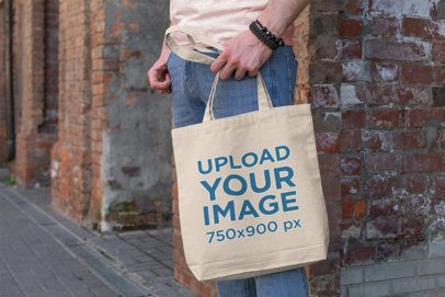 Mockup of a Man Holding a Tote Bag Next to a Brick Wall 192-el