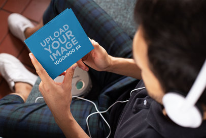 Mockup of a Man Holding a Digipak While Listening to Music 28354