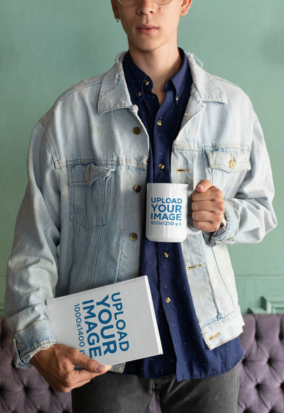 Mockup of a Man Wearing a Denim Jacket and Holding a Coffee Mug and a Book 28465