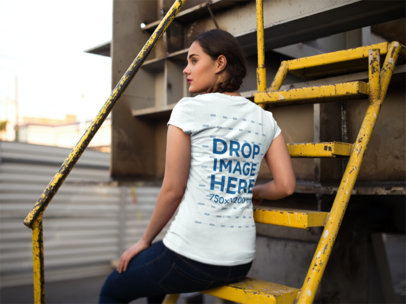 Girl Sitting on a Yellow Stairway Wearing a T-Shirt Mockup from the Back a9091b