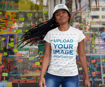 T-Shirt Mockup of a Woman with a Dad Hat Standing in Front of a Display Window 28562