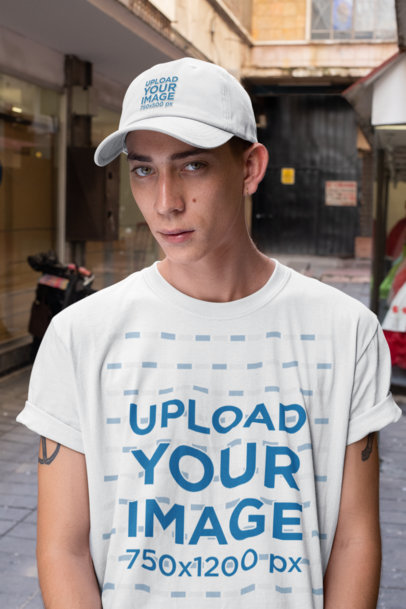 Mockup of a Young Man Wearing a T-Shirt and a Dad Hat in an Alley 28592
