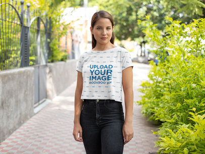 Mockup of a Woman Wearing a Sublimated Crop Top on a Street 28559
