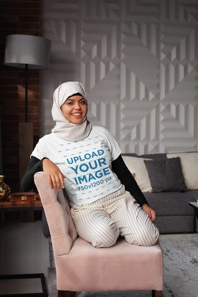T-Shirt Mockup of a Woman Wearing a Hijab Casually Sitting on a Couch 28399