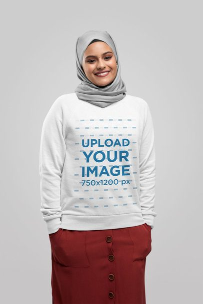 Sweatshirt Mockup Featuring a Happy Woman with a Hijab Against a Plain Background 28389