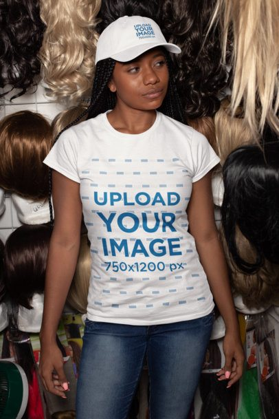 T-Shirt Mockup of a Woman Wearing a Dad Hat Against a Wall of Wigs 28571