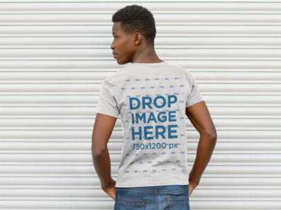 Back Mockup of a Guy Wearing a T-Shirt Facing a Steel Rollup Door a9281b