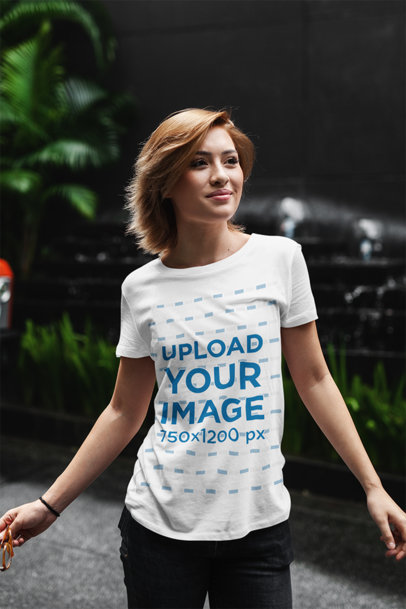 T-Shirt Mockup of a Young Woman Standing Against a Dark Background with Some Plants 411-el