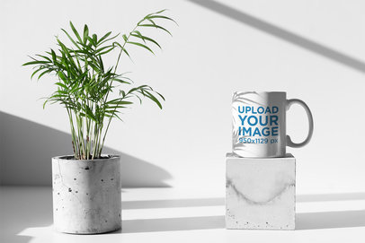 Mockup of an 11 Oz Coffee Mug Standing on a Pedestal Next to a Concrete Plant Pot 396-el
