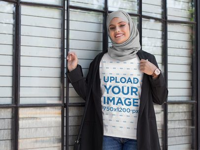 T-Shirt Mockup of a Woman Wearing a Hijab and Standing Next to a Large Window 28385