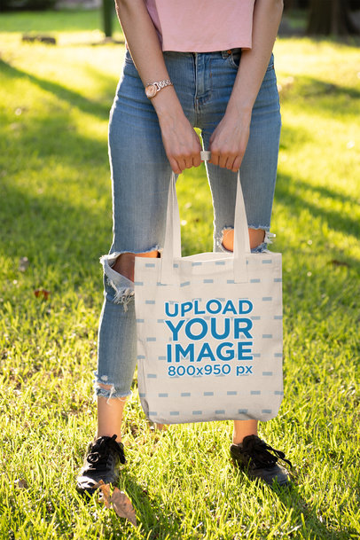 Mockup of a Woman Holding a Tote Bag with Both Hands