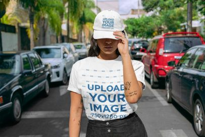 Mockup of a Woman Standing in the Street Wearing a T-Shirt and a Dad Hat 28608