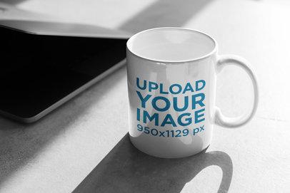 11 oz Coffe Mug Mockup Beside a Semi-Open Laptop 403-el