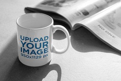11 oz Coffee Mug Mockup Beside a Newspaper 404-el