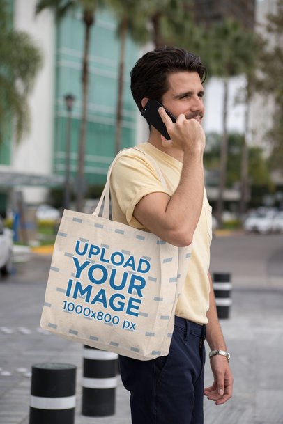 Tote Bag Mockup Featuring a Trendy Man Talking on His Smartphone