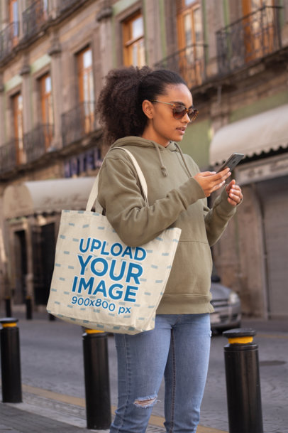 Tote Bag Mockup of a Woman in the Street Checking Her Phone 28848