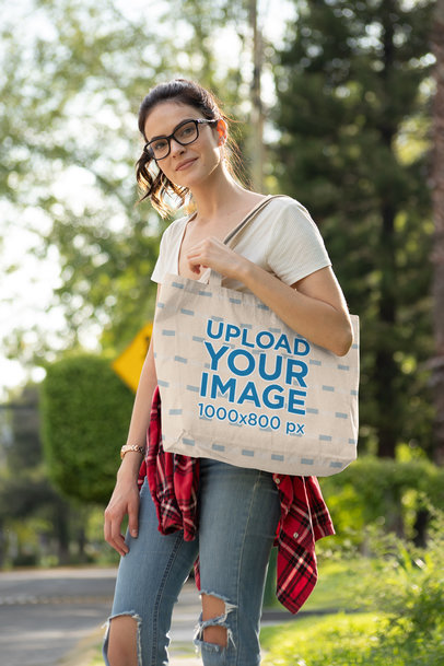 Tote Bag Mockup Featuring a Woman with Glasses Wearing Ripped Jeans 28836