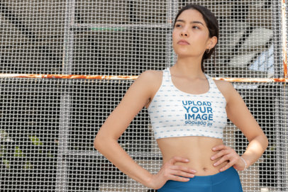Mockup of a Fit Woman Wearing a Sports Bra and Leggings by a Mesh Fence 28712