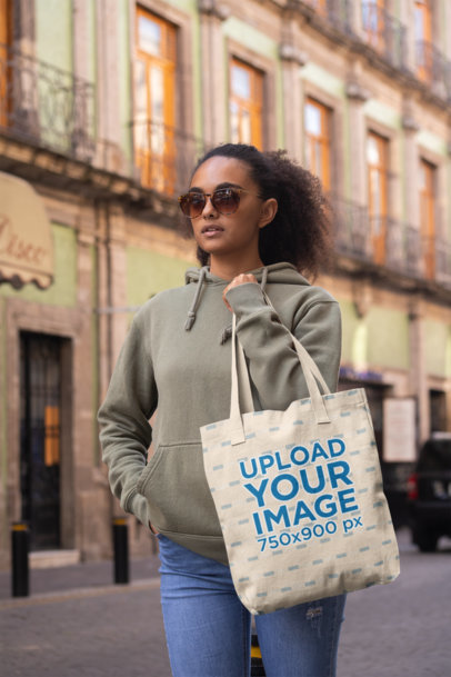 Tote Bag Mockup Featuring a Trendy Woman Walking by an Old Building 28871