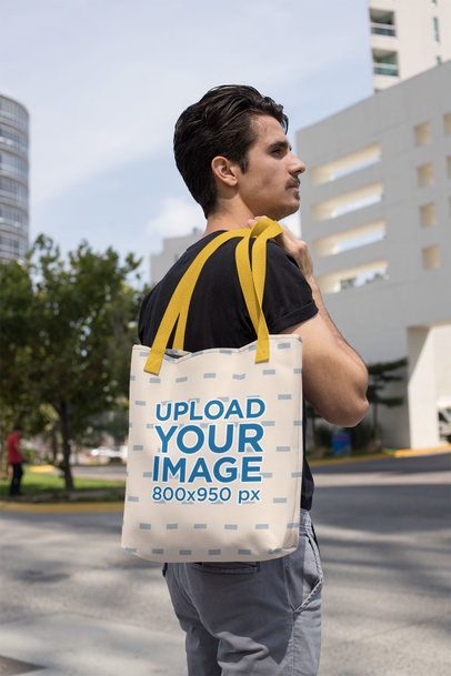Mockup of a Man Holding a Tote Bag with a Customizable Strap over His Shoulder 28853