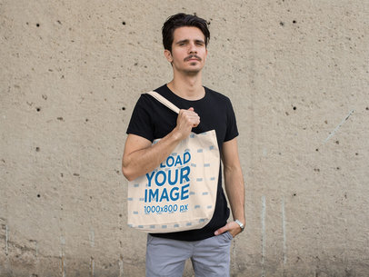 Mockup of a Man Holding a Tote Bag with a Concrete Wall in the Background