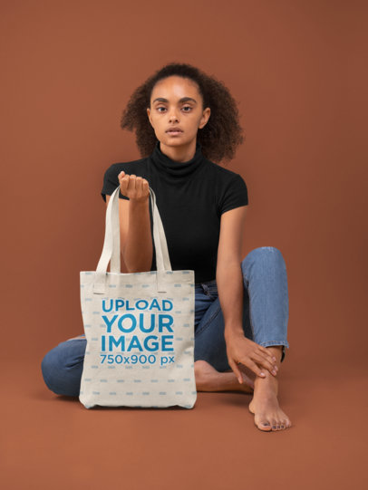 Tote Bag Mockup Featuring a Woman Sitting Against a Solid Color Background 28866