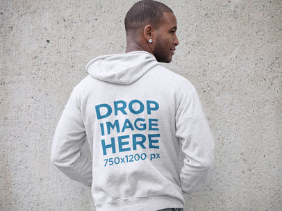 Mockup of a Black Man Wearing a Pullover Hoodie Facing a Wall a9316b