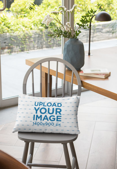 Mockup Featuring a Pillow Lying on a Grey Wooden Chair by a Table 29002