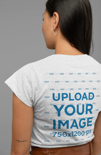 Mockup of a Woman Wearing a Heather T-Shirt and Facing the Studio Wall 28760