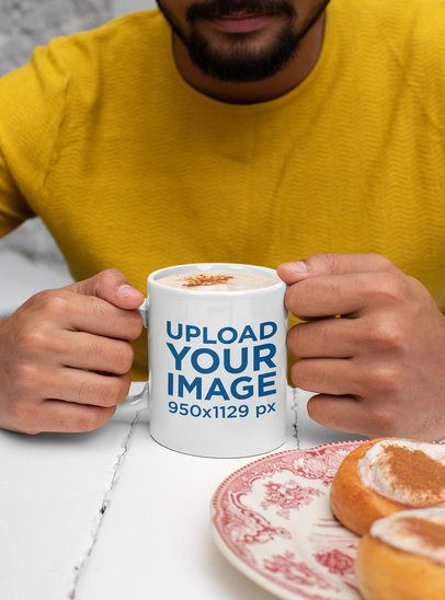 Mockup of a Bearded Man Holding an 11 oz Mug in Front of Some Bagels 29099
