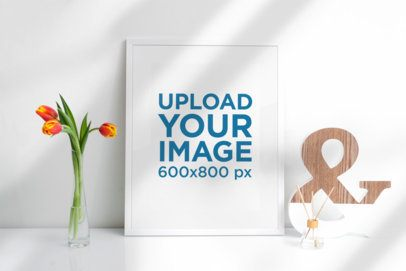 Mockup of a Picture Frame Standing Against a White Wall and Next to a Flower Vase 501-el