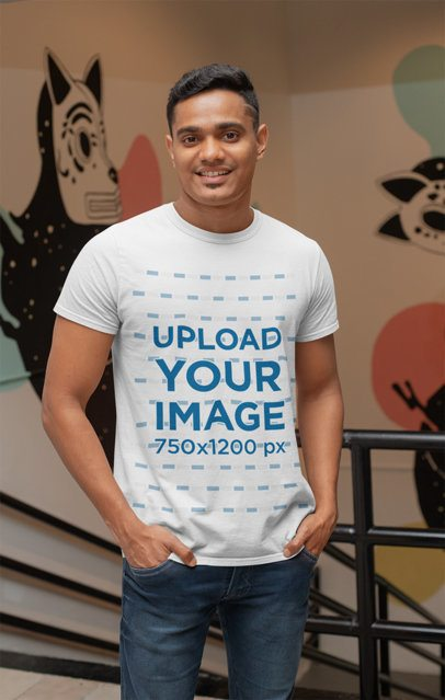 T-Shirt Mockup of a Man Standing by a Wall with Paintings 28960