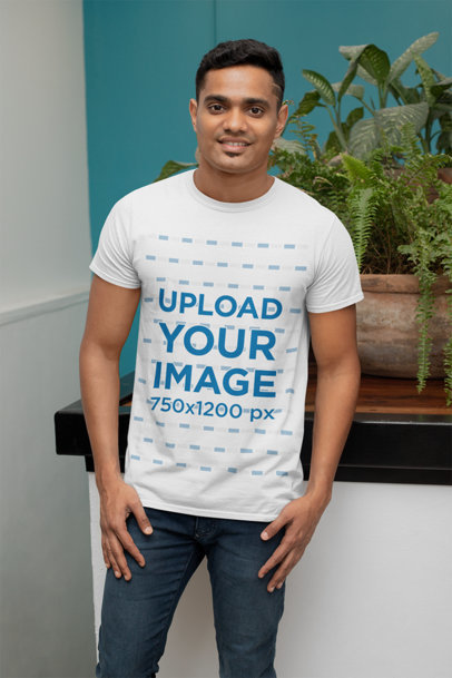 Mockup of a Man with a T-Shirt Posing Next to a Plant 28956