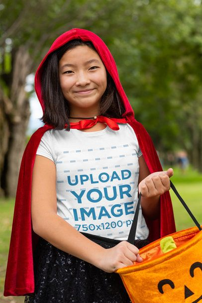 T-Shirt Mockup of a Happy Girl in a Red Coat Holding a Pumpkin Bag 29281