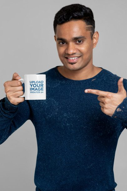Mockup of a Man Holding an 11 oz Mug and Pointing at It 28964