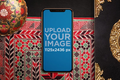 Mockup of an iPhone X in Portrait Position Featuring a Colorful Cloth 671-el