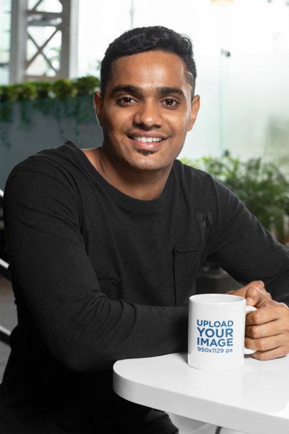 11 oz Coffee Mug Mockup Featuring a Joyful Man Sitting at a White Table 28965