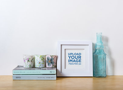 Photo Frame Mockup Standing on a Wooden Table Next to a Glass Bottle 587-el