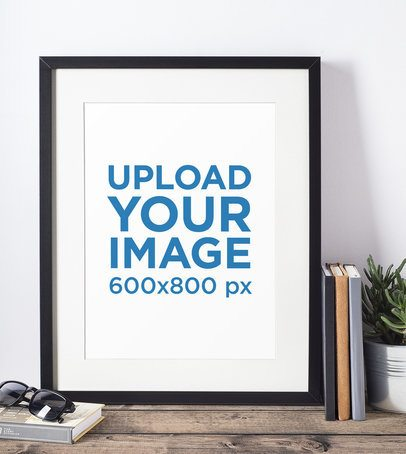 Mockup of a Picture Frame Standing on a Wooden Table and Against a White Wall 600-el